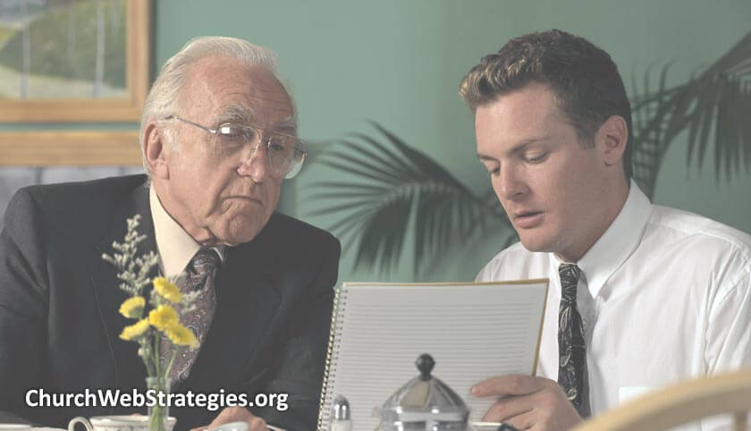 Older and younger businessmen looking at notebook